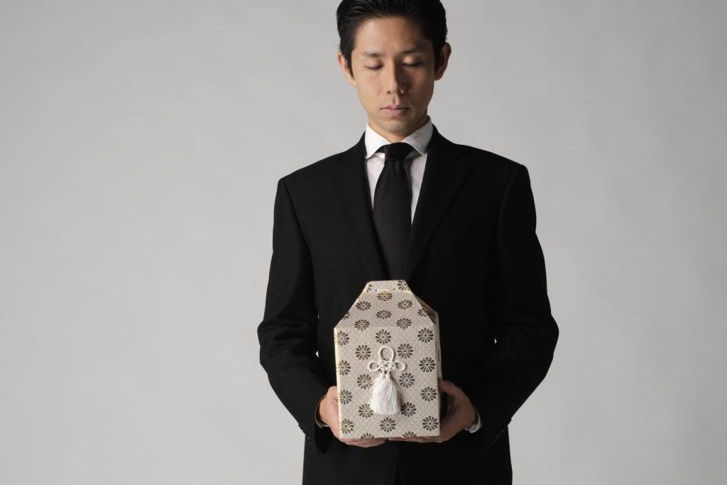 骨壷を持つ人の写真